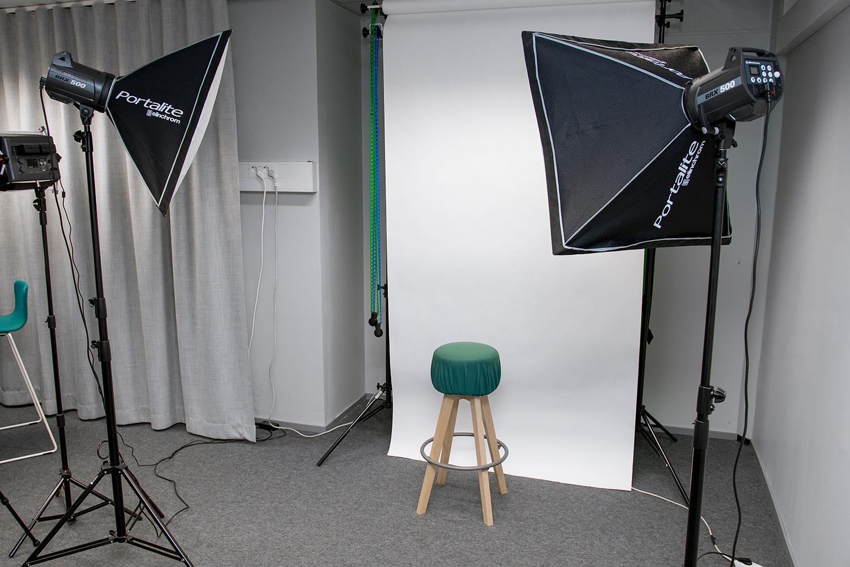 Kuvaustausta, jossa on taustakartongin edessä oleva jakkara ja kaksi kuvausvaloa.