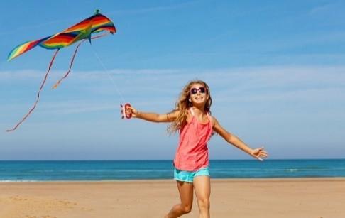 Esimerkkikuva, jossa tyttö lennättää värikästä leijaa rannalla.